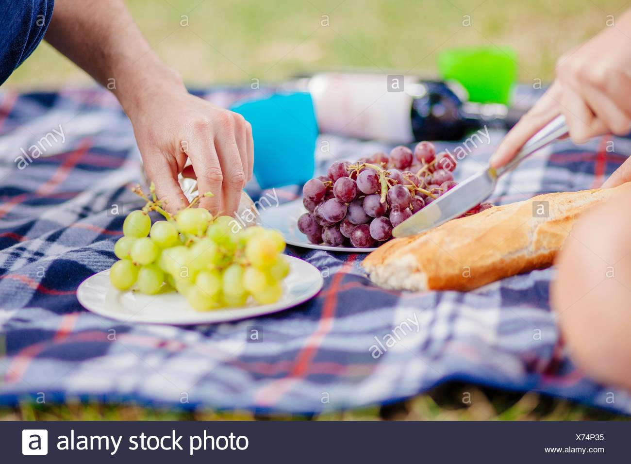 Cropped view of couples hands reaching for grapes on picnic blanket - Stock Image