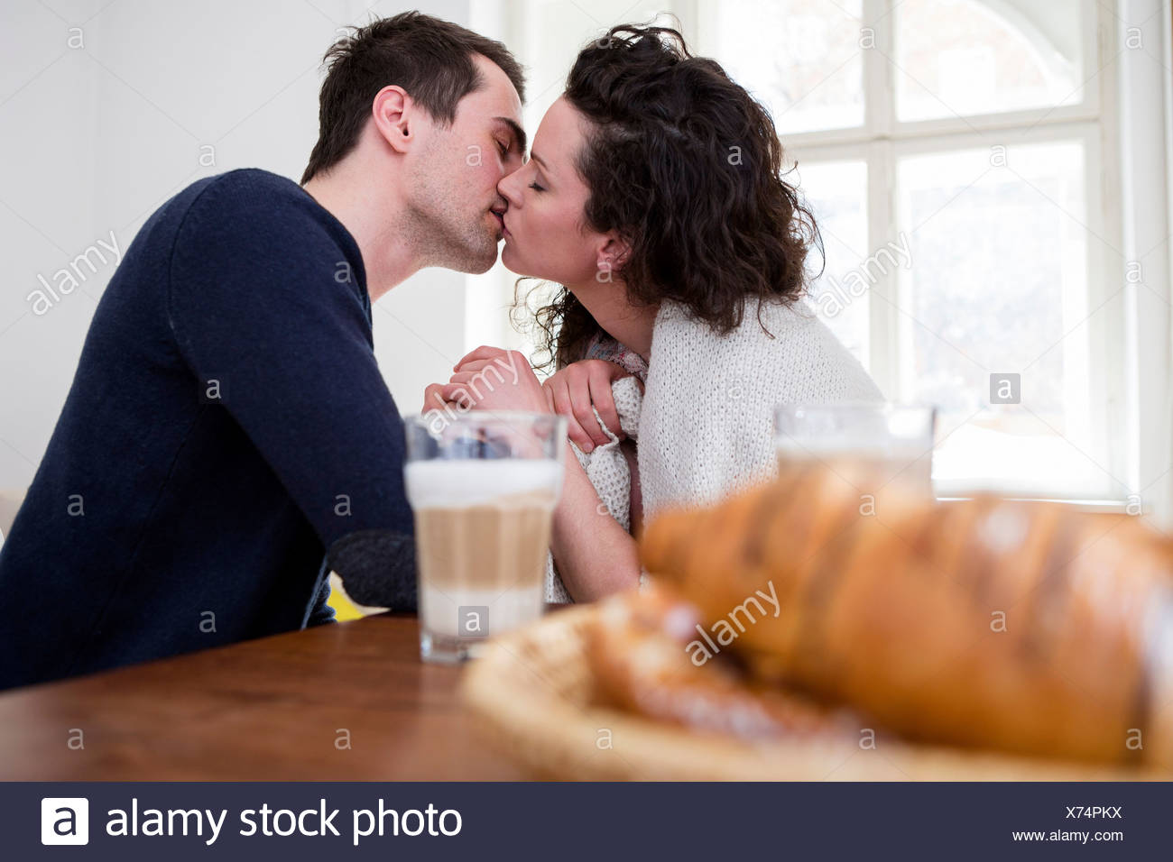 Heterosexual couple kissing at breakfast table - Stock Image