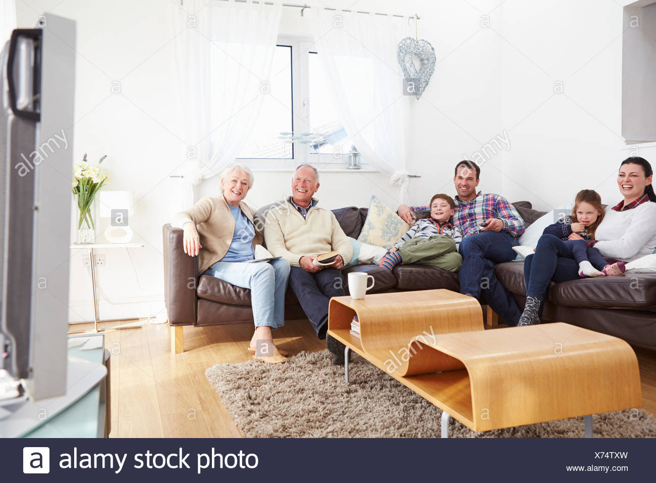 Multi Generation Family Watching TV Together - Stock Image