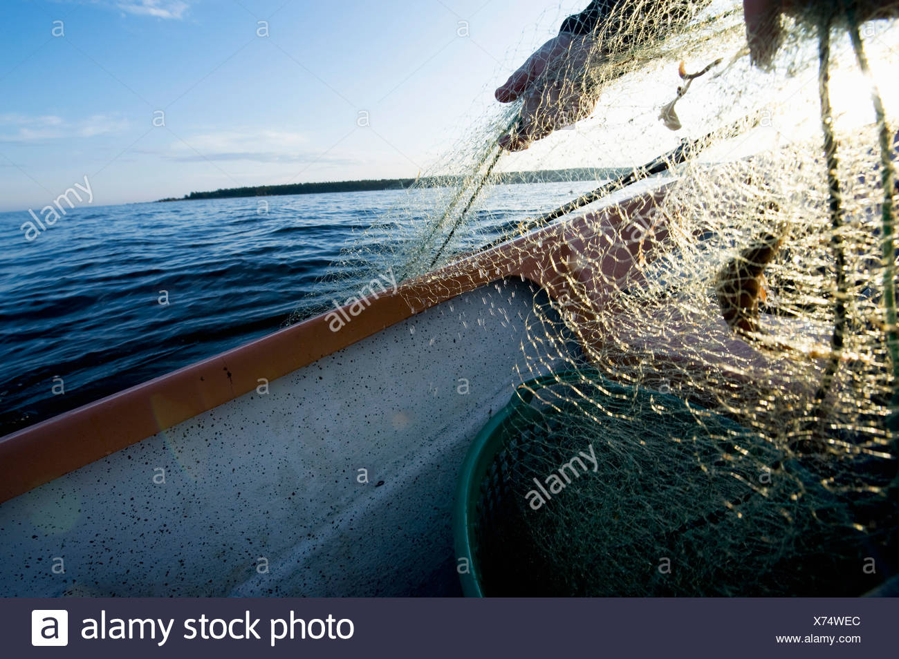 Man bring up fishing net - Stock Image