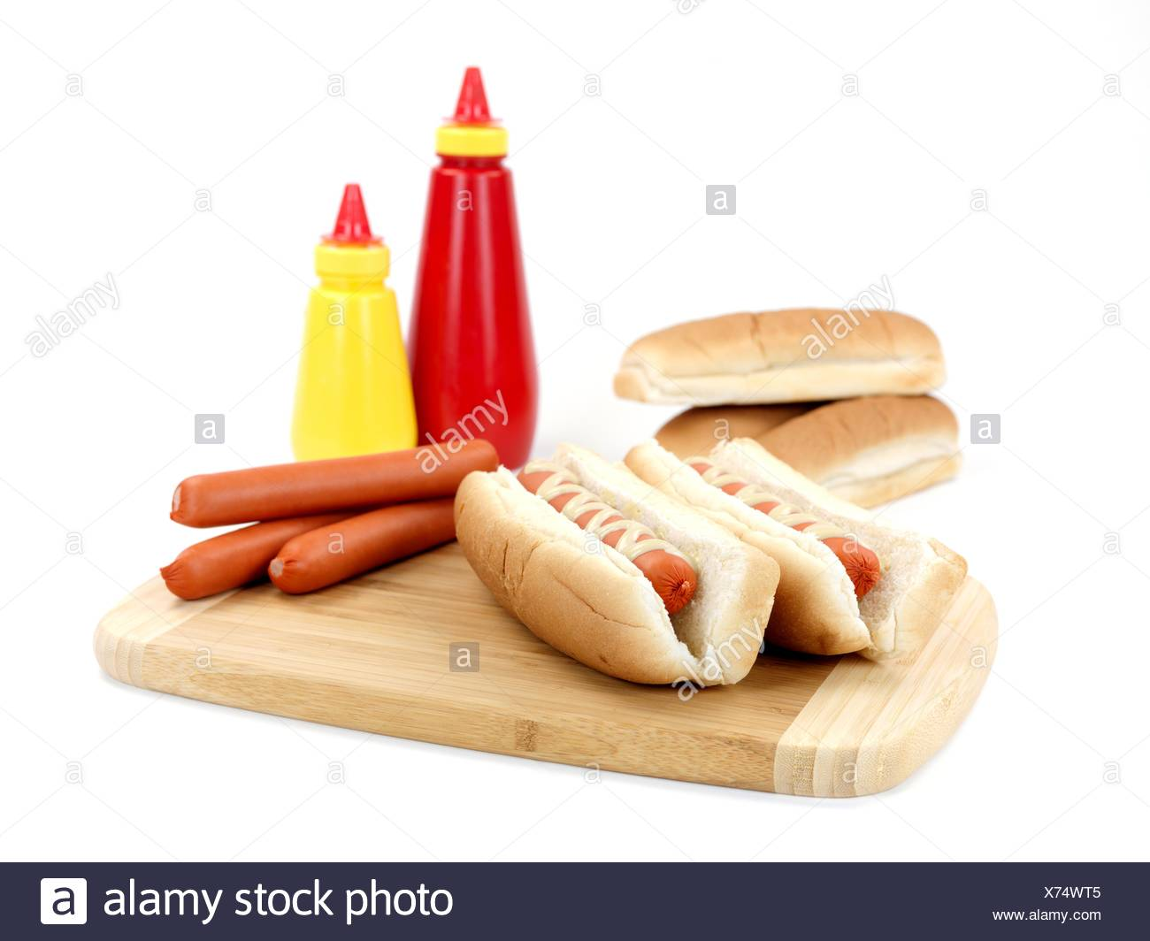 A hotdog with mustard sauce on a kitchen bench - Stock Image