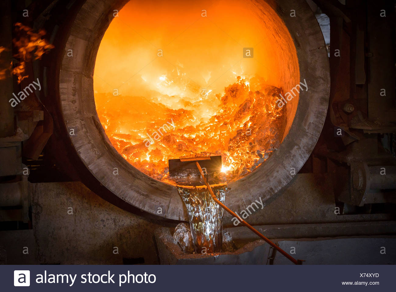 Raking liquid aluminum from furnace at recycling plant - Stock Image