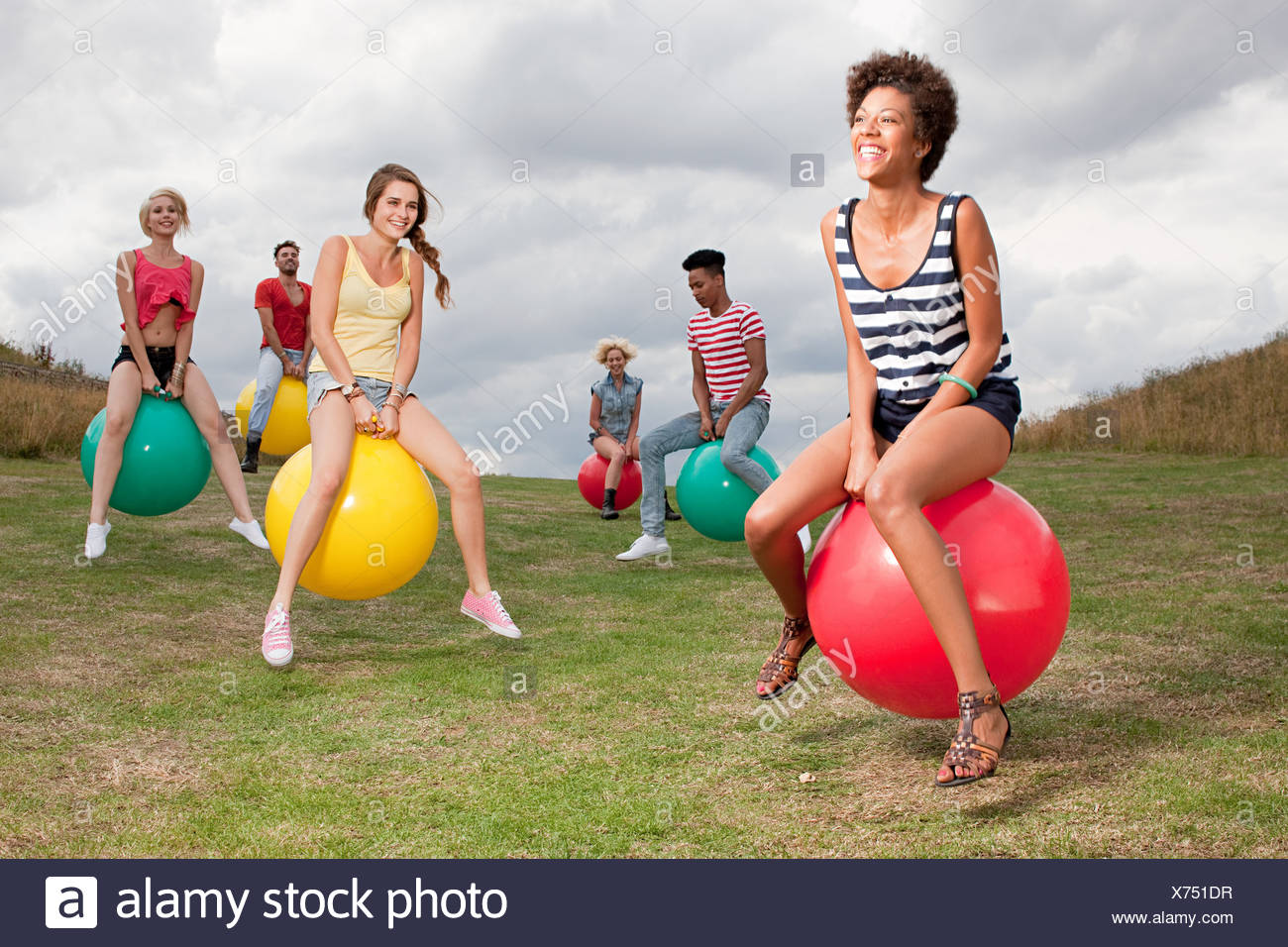 Young people bouncing on hoppity horses - Stock Image
