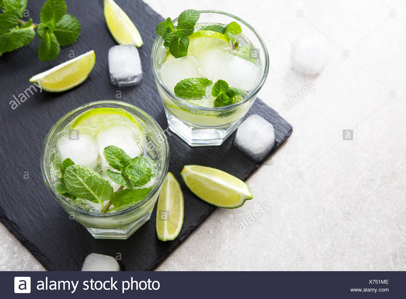 Cold refreshing summer lemonade mojito in a glass on a slate board and stone background. - Stock Image