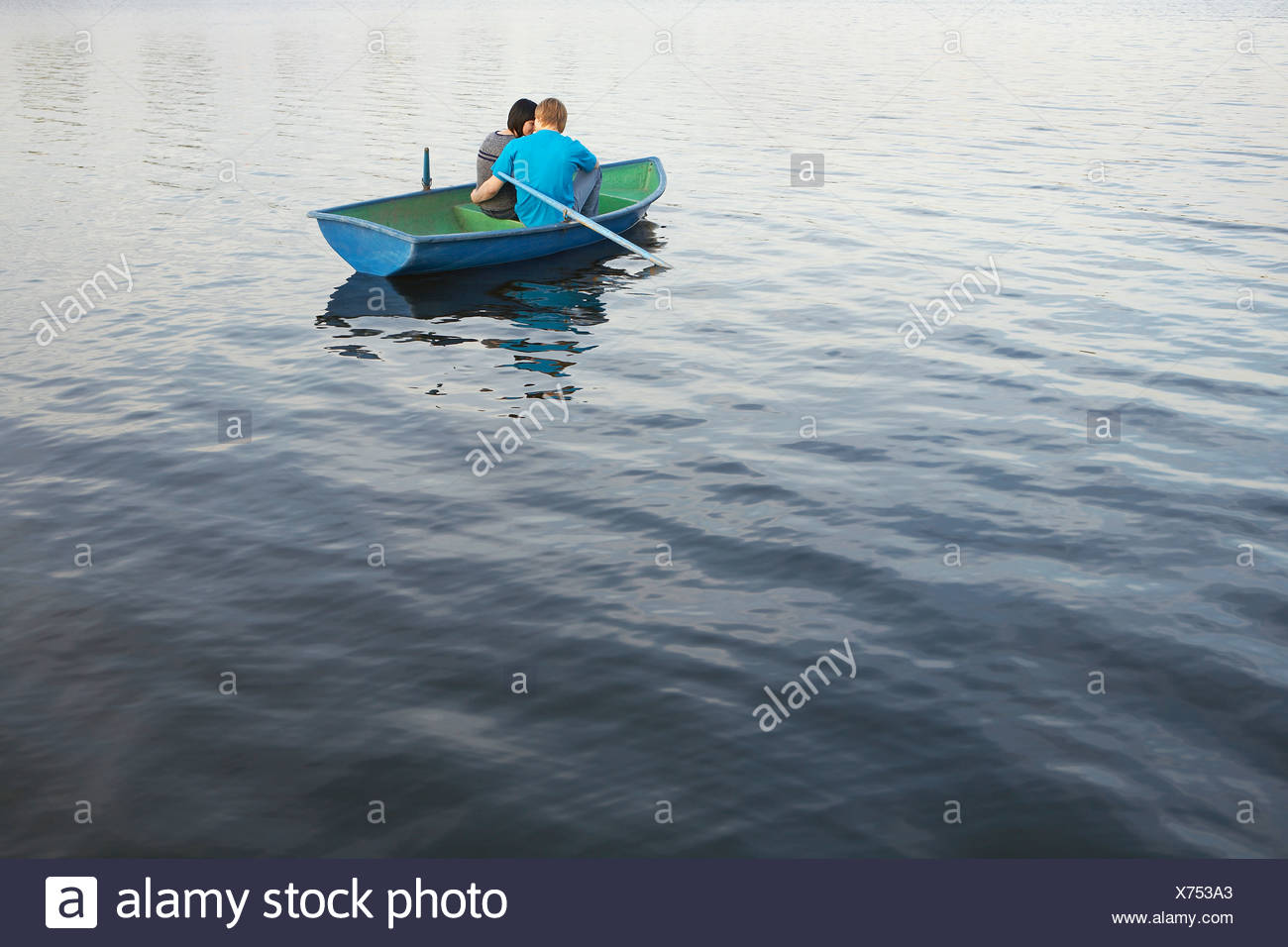 Young Couple Cuddling in Rowboat on Lake - Stock Image