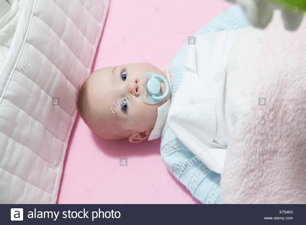 Awake four month baby boy lying in cot with bumper pad. Overhead view. Stock Photo