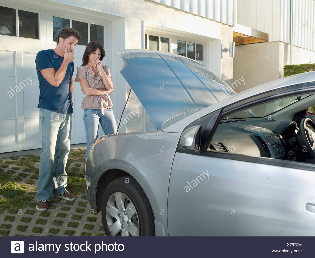 Confused couple looking at car engine - Stock Image