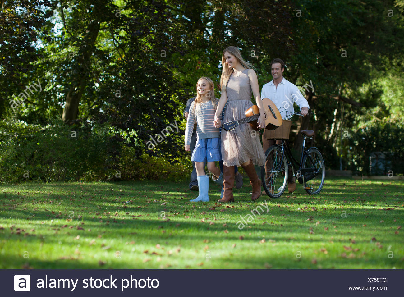 Multi-generation family with bicycle and guitar in orchard Stock Photo