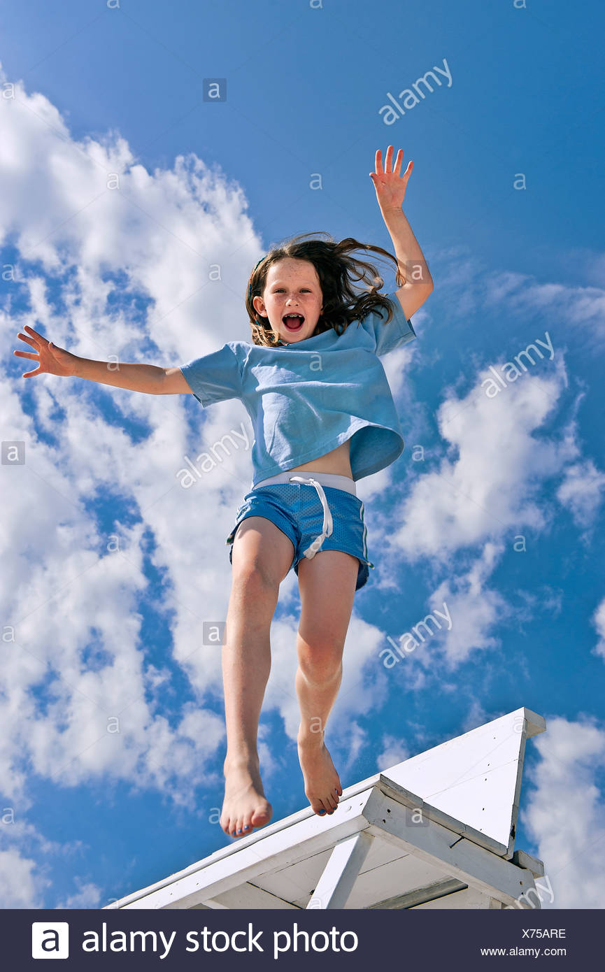 Girl jumping from a beach chair.5t - Stock Image