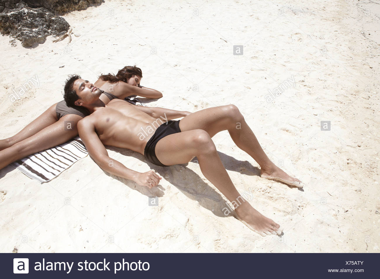 A couple sunbathing. - Stock Image