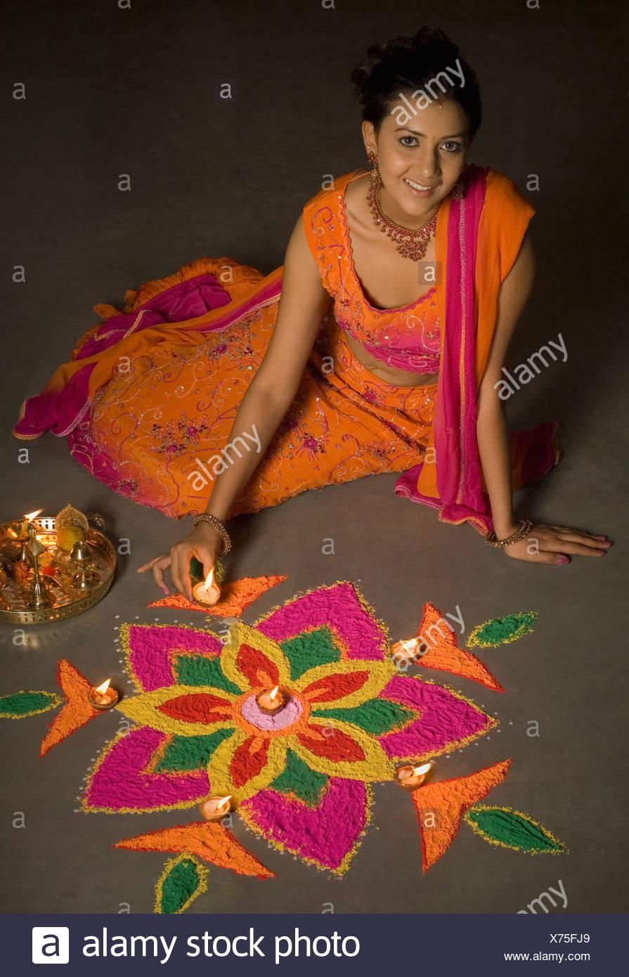 Portrait of a young woman making a rangoli Stock Photo