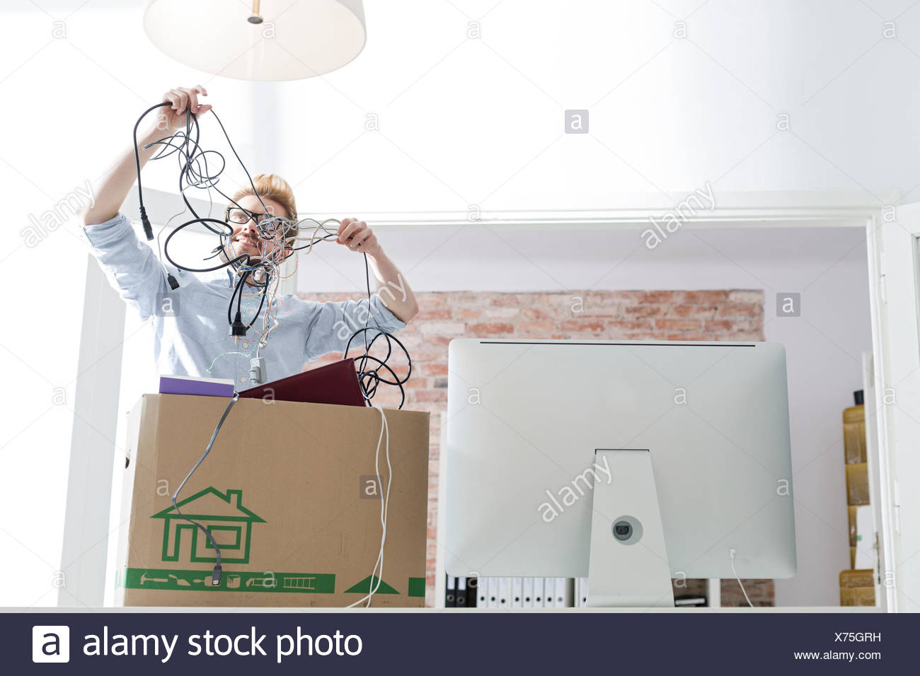 Young man with cable tangle in office - Stock Image
