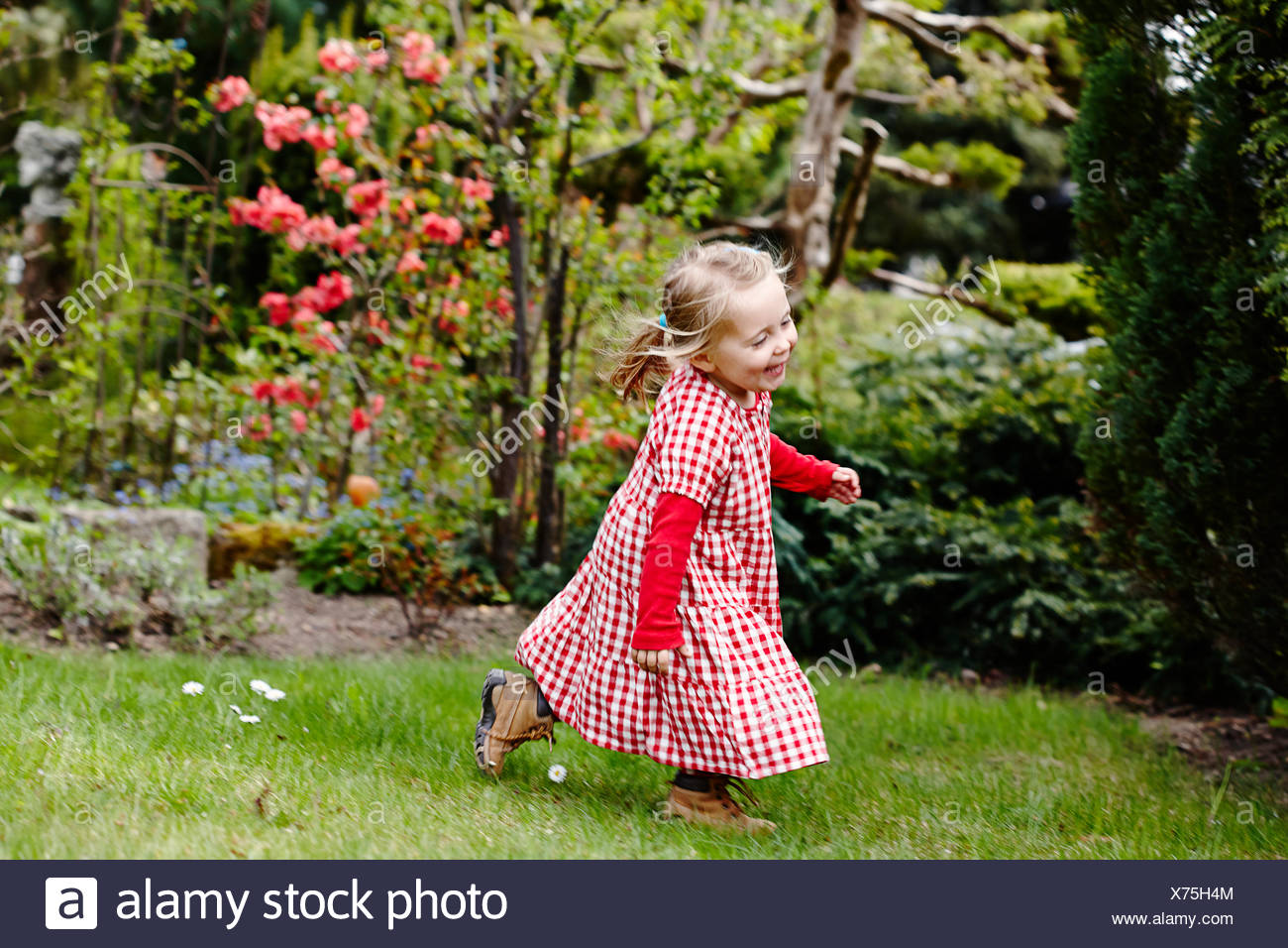 Young girl wearing gingham dress running in garden - Stock Image