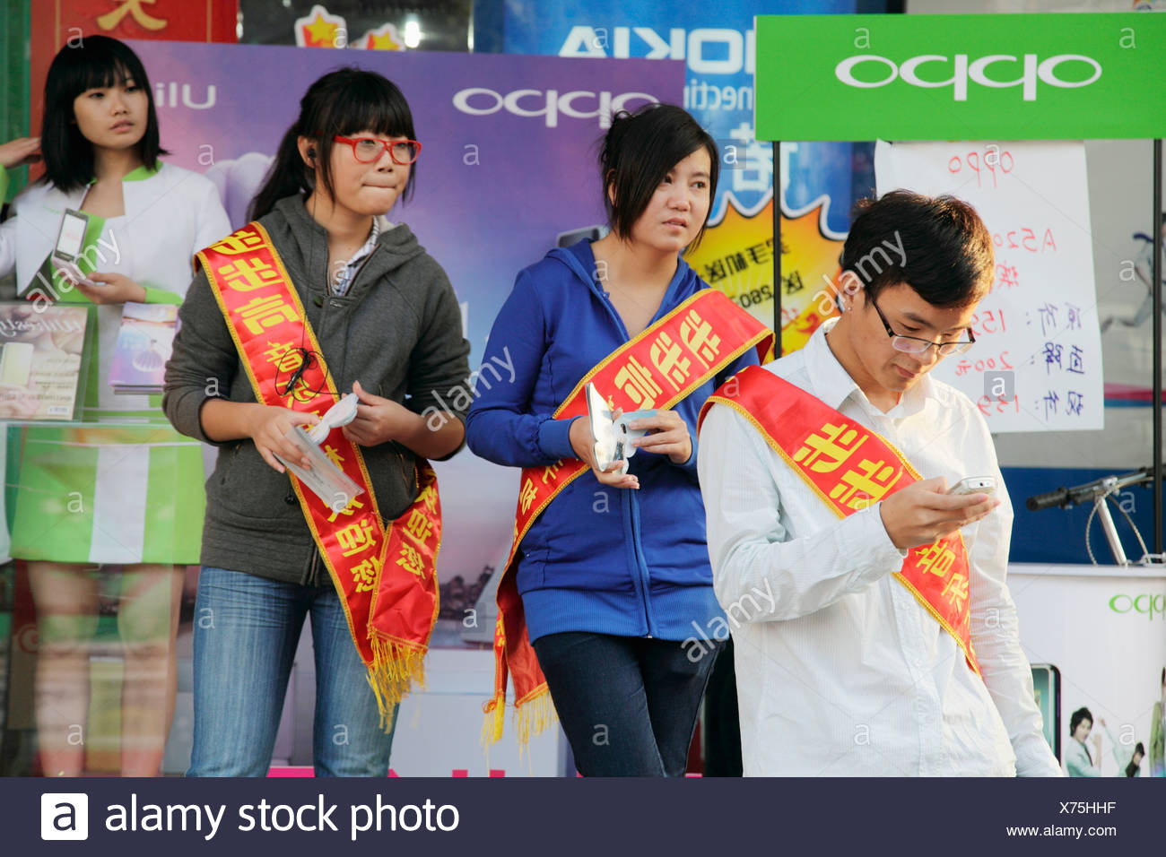 Collage students doing promotional work for department store in downtown of Sanya  Sanya  China. - Stock Image
