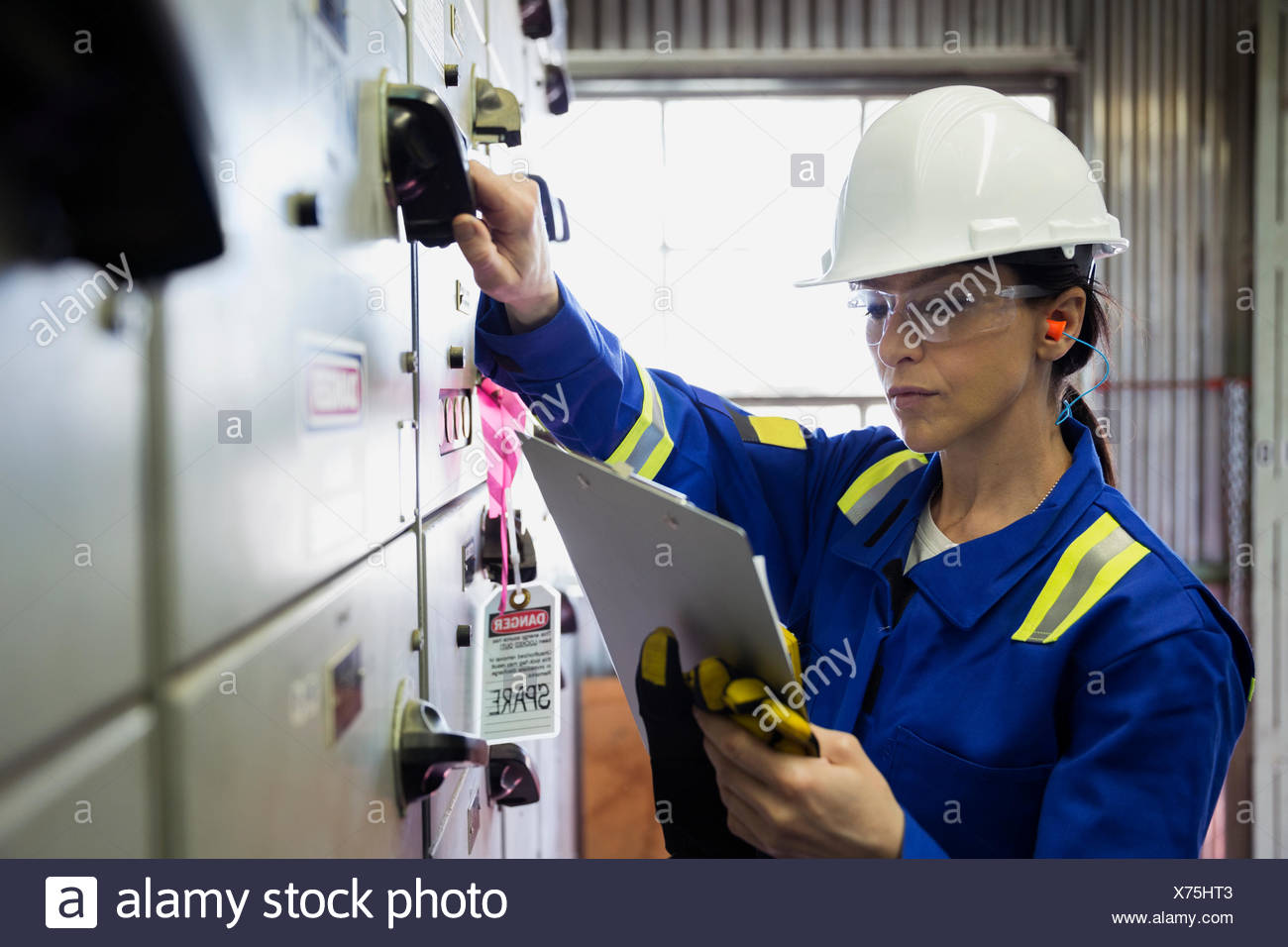 Female worker at control panel in gas plant - Stock Image