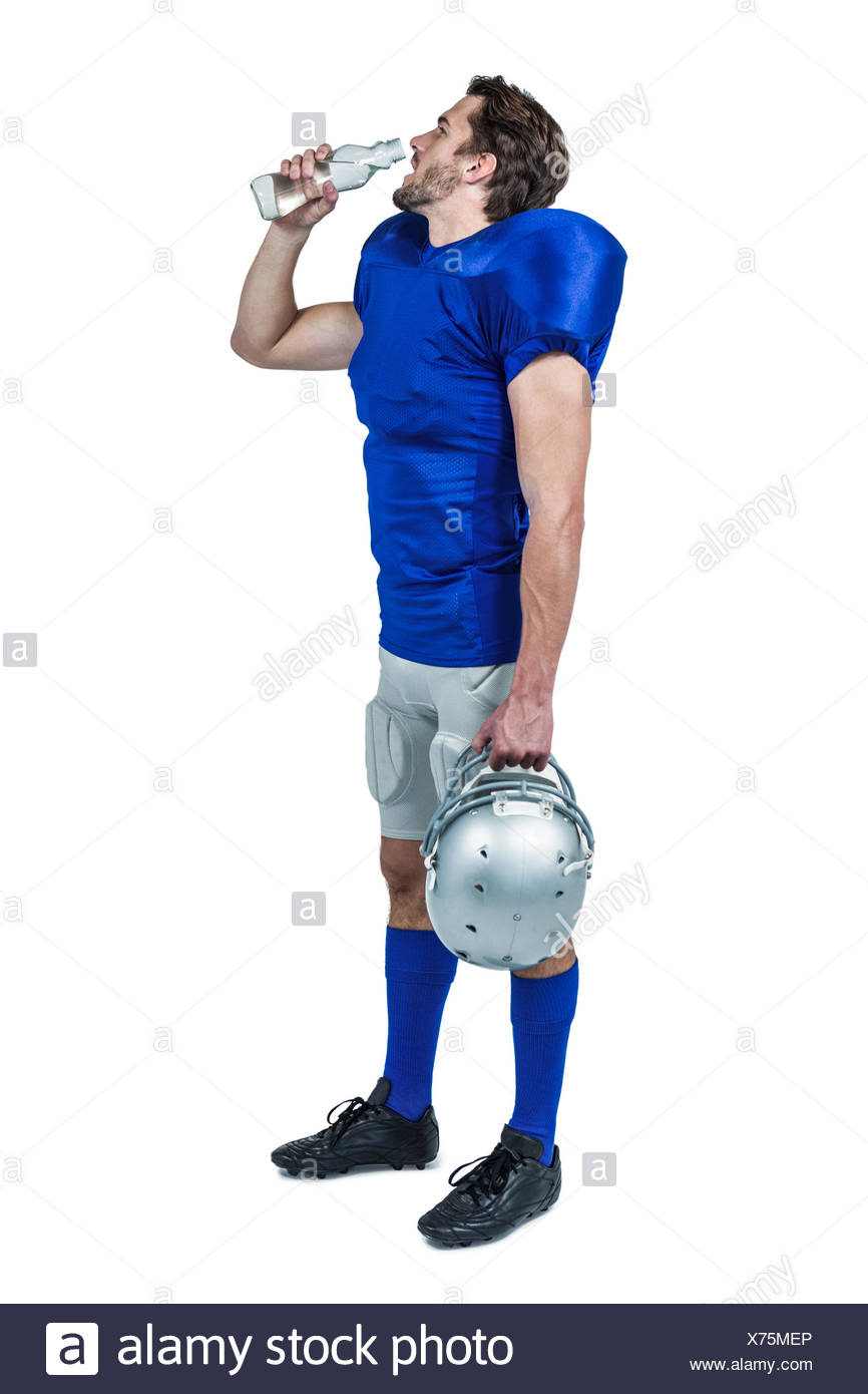Full length of American football player holding helmet while drinking water - Stock Image