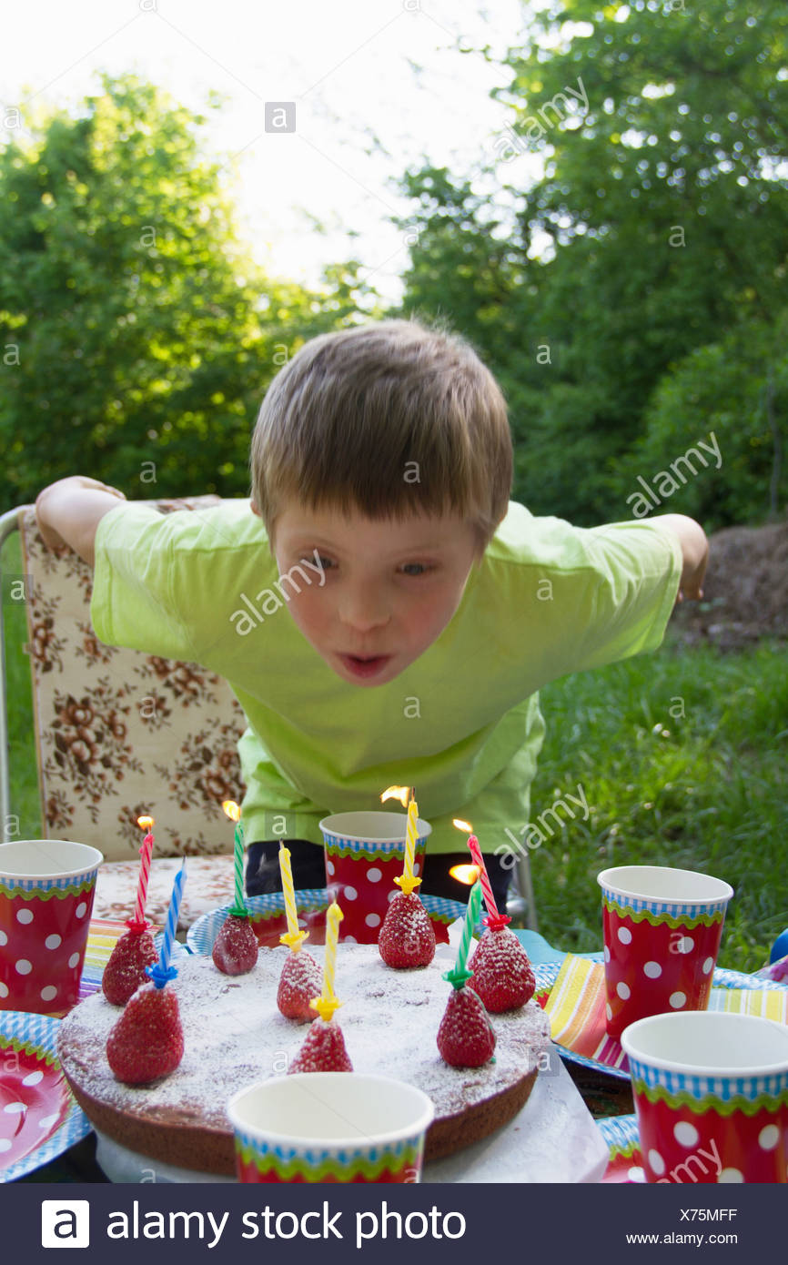 Close up portrait of young boy blowing out birthday candles - Stock Image