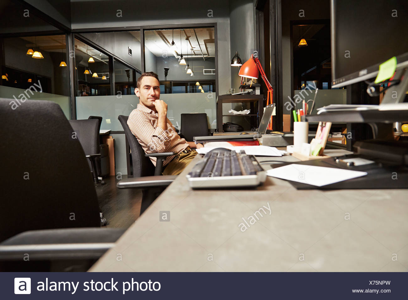 Portrait of businessman sitting at desk in office - Stock Image