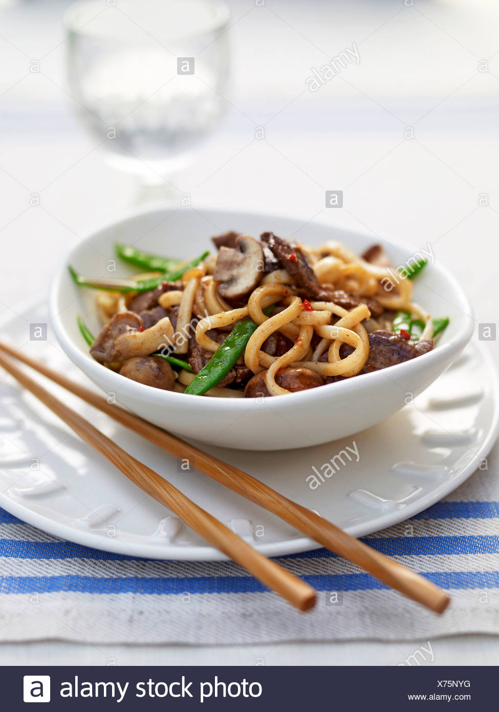 Bowl of ginger beef noodles on plate, close-up - Stock Image