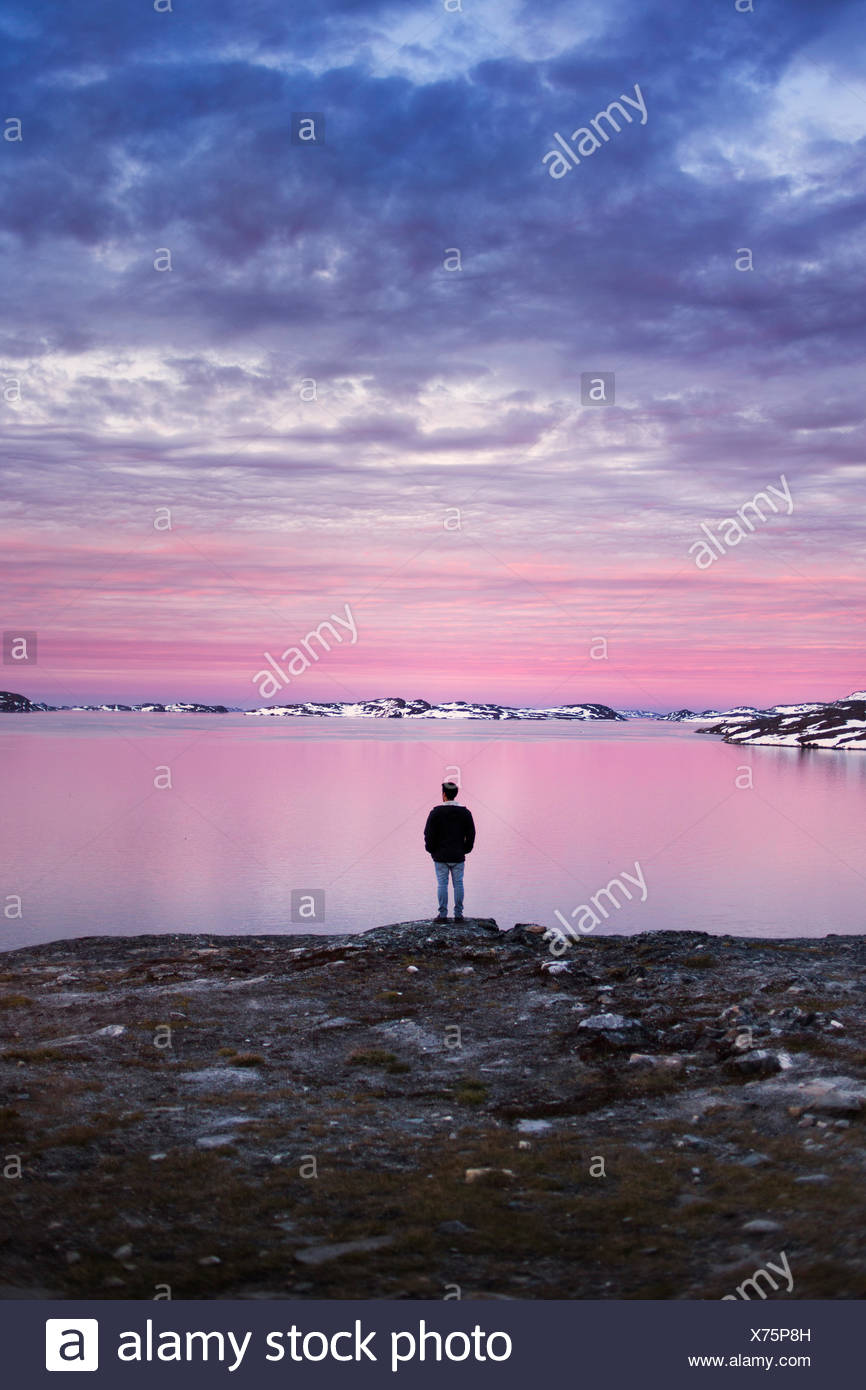 Full length rear view of young man on shore enjoying the sunset view during winter - Stock Image