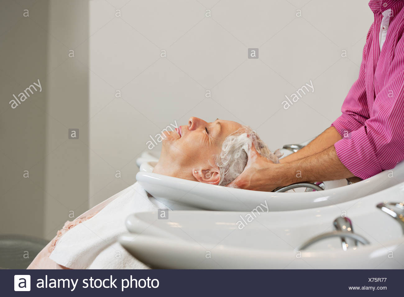 A senior woman having her hair shampooed at a hairdressing salon, close up - Stock Image