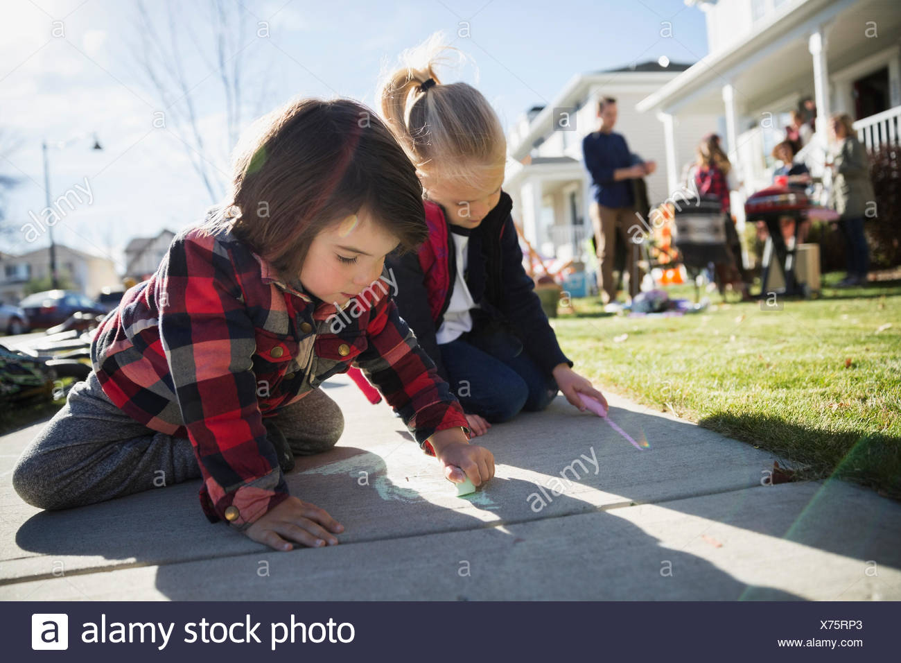 Kids drawing on sidewalk with chalk - Stock Image