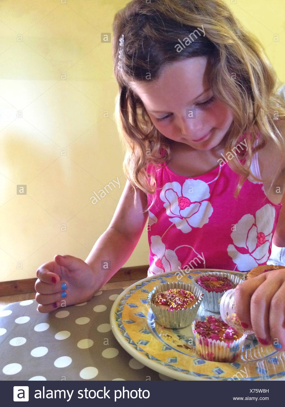 Girl decorating cupcakes - Stock Image