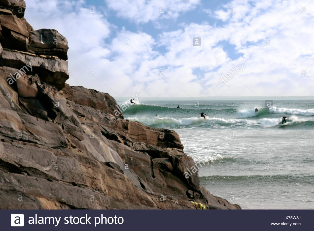 beautiful clean atlantic ocean with surfers catching the waves with cliffs in foreground on Irelands coast - Stock Image