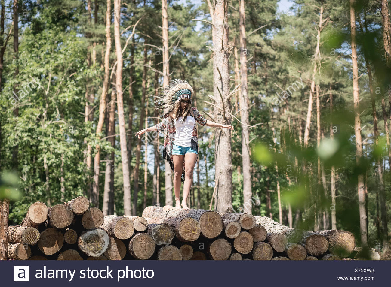Young woman masquerade as an Indian balancing on stack of wood - Stock Image