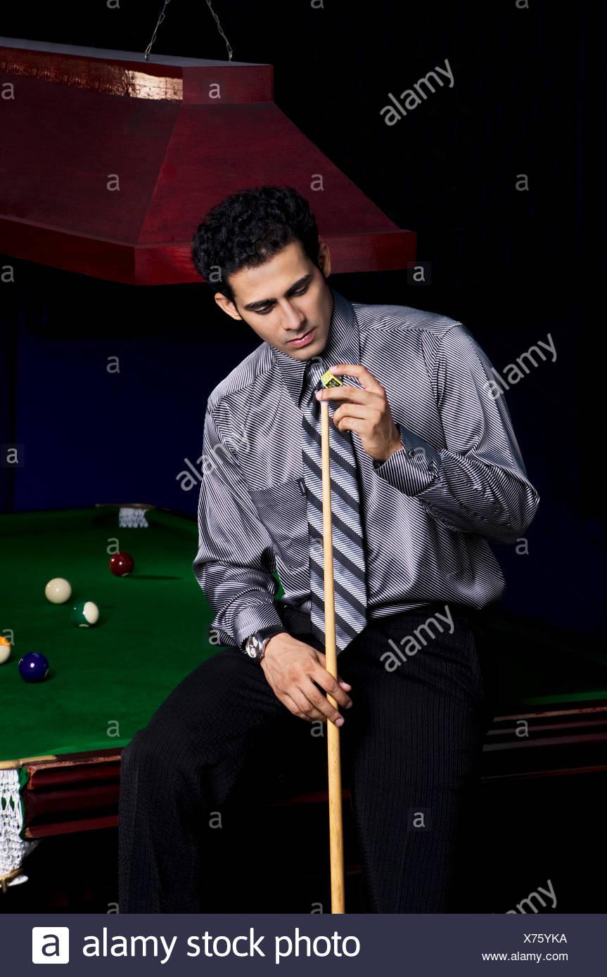 Man applying chalk to cue stick - Stock Image