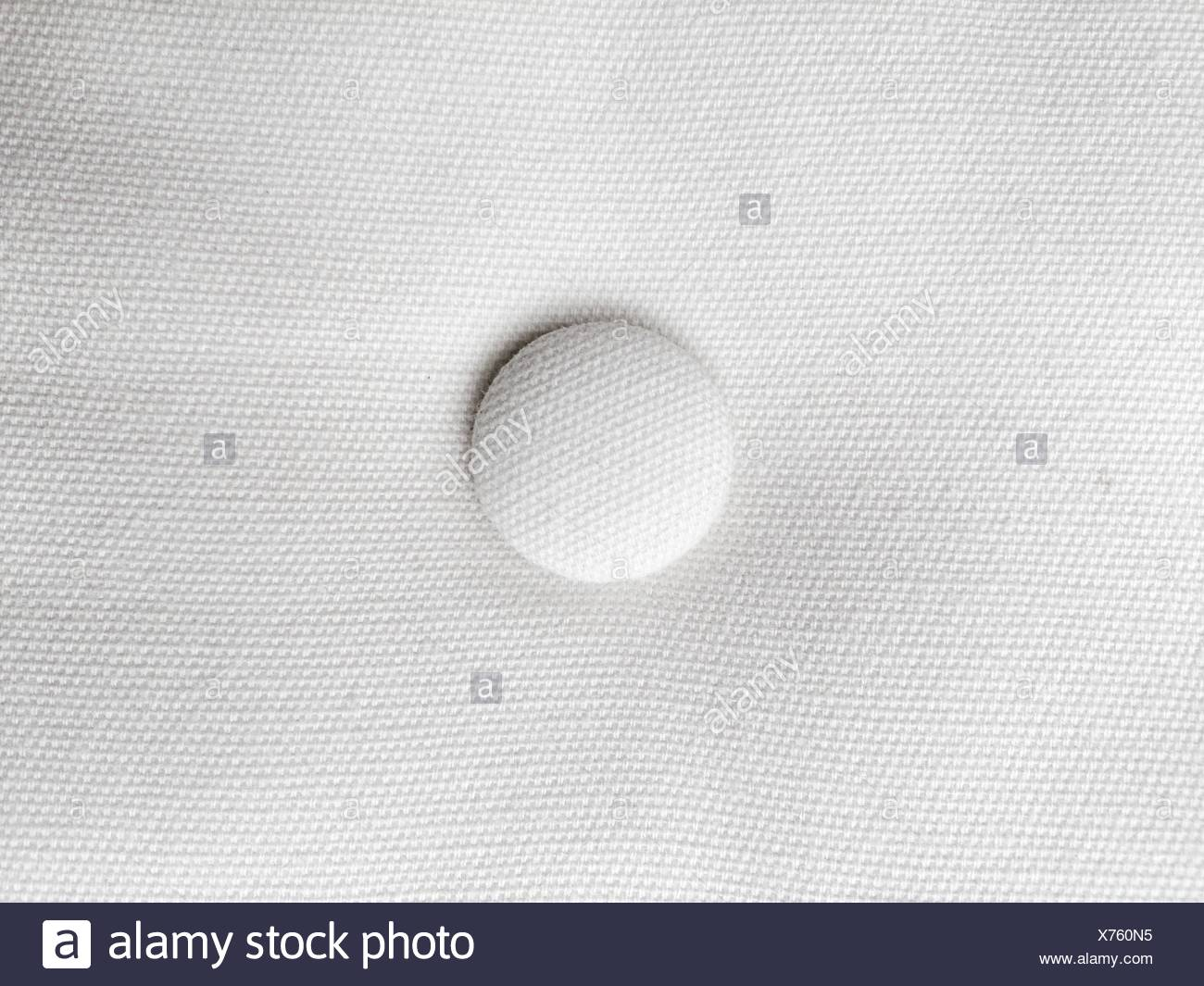 Close-Up Of Button On White Fabric - Stock Image