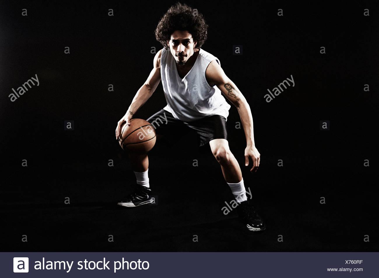 Basketball player bouncing basketball - Stock Image