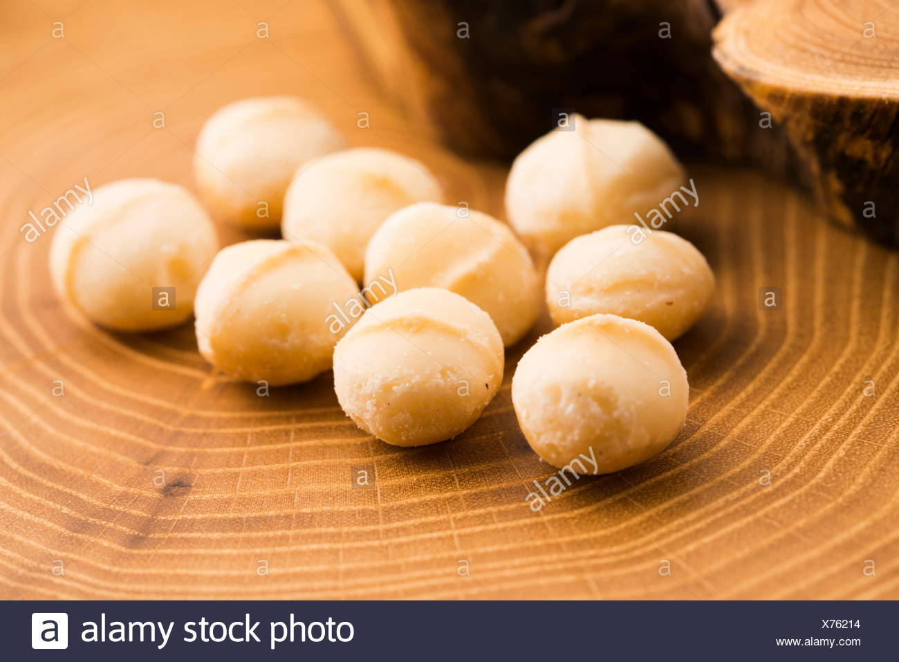 Roasted Macadamia nuts on rustic wooden background - Stock Image