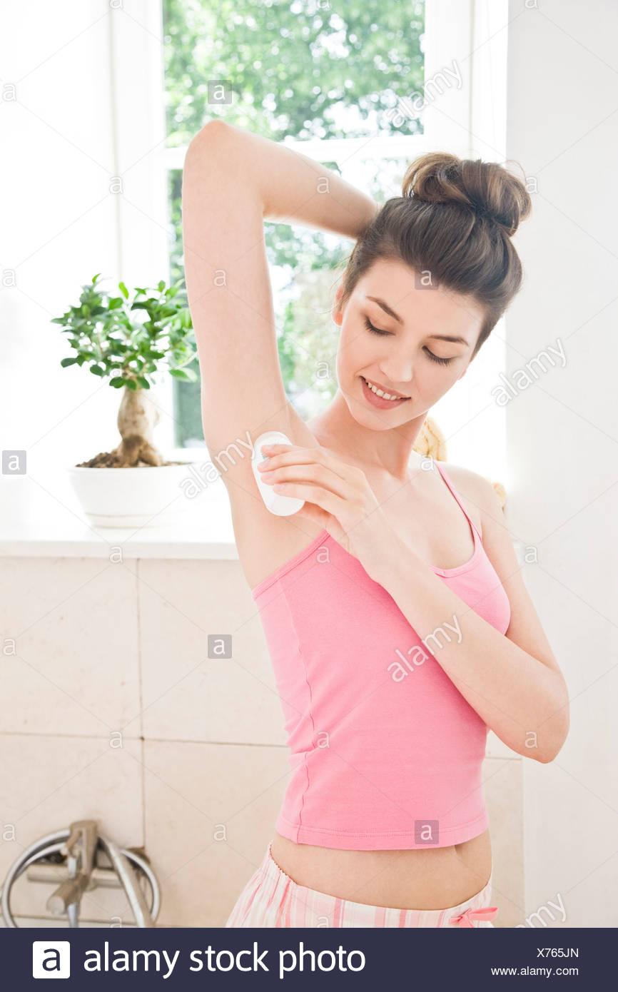 woman applying deodorant - Stock Image