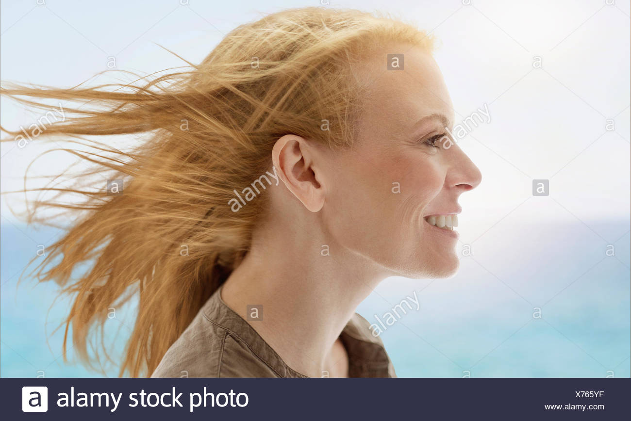 Portrait of woman by sea - Stock Image