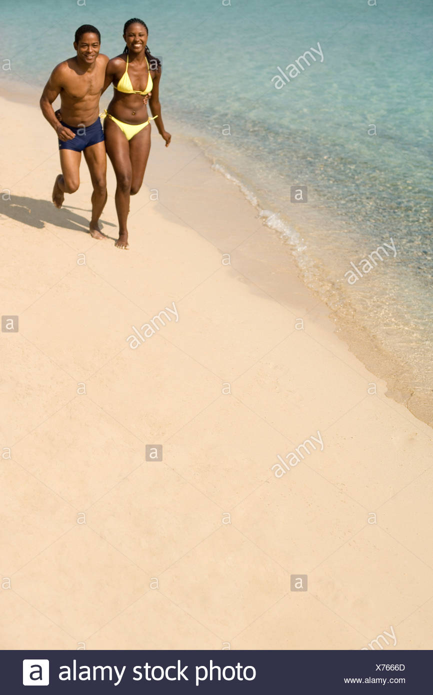 Couple jogging along a beach. - Stock Image