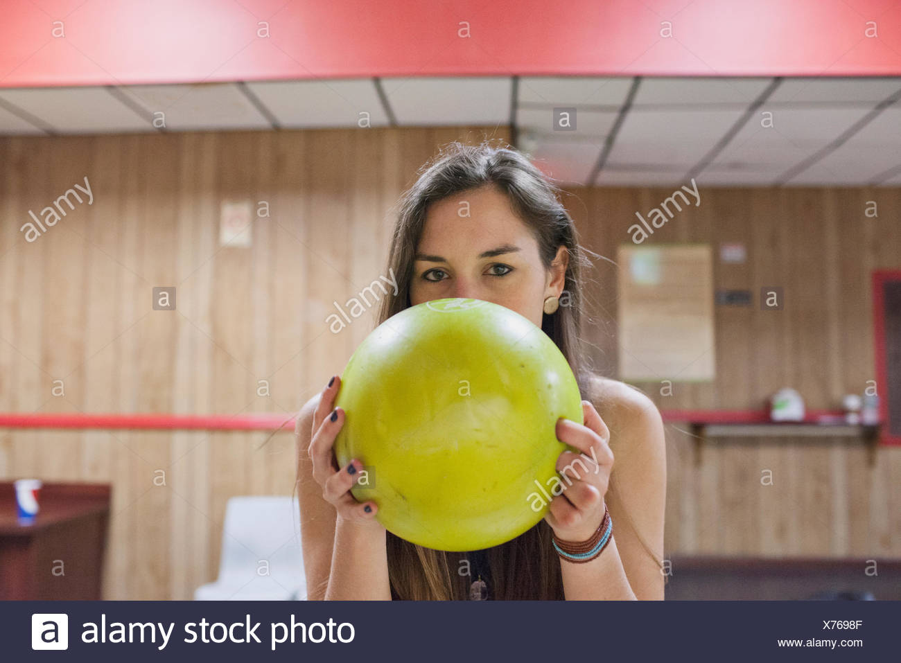 A young woman with a yellow bowling ball. - Stock Image