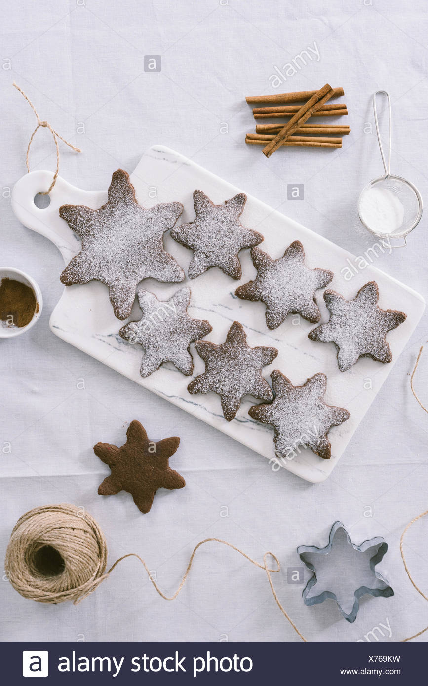 Chocolate Cinnamon Snowflake Cookies dusted with powdered sugar served on a white marble board. - Stock Image