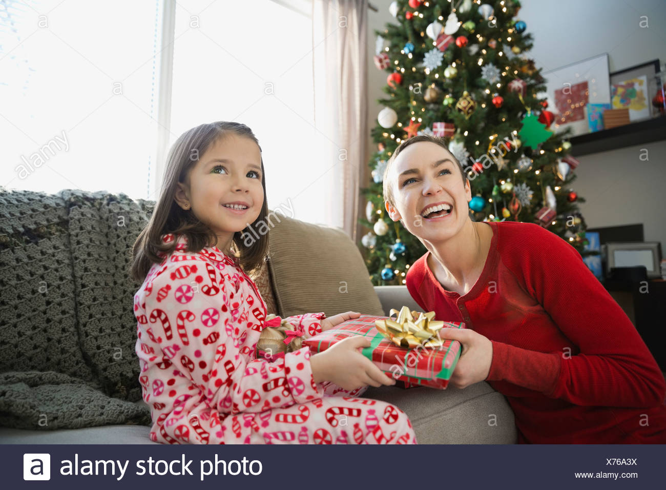 Mother and daughter exchanging Christmas gift - Stock Image