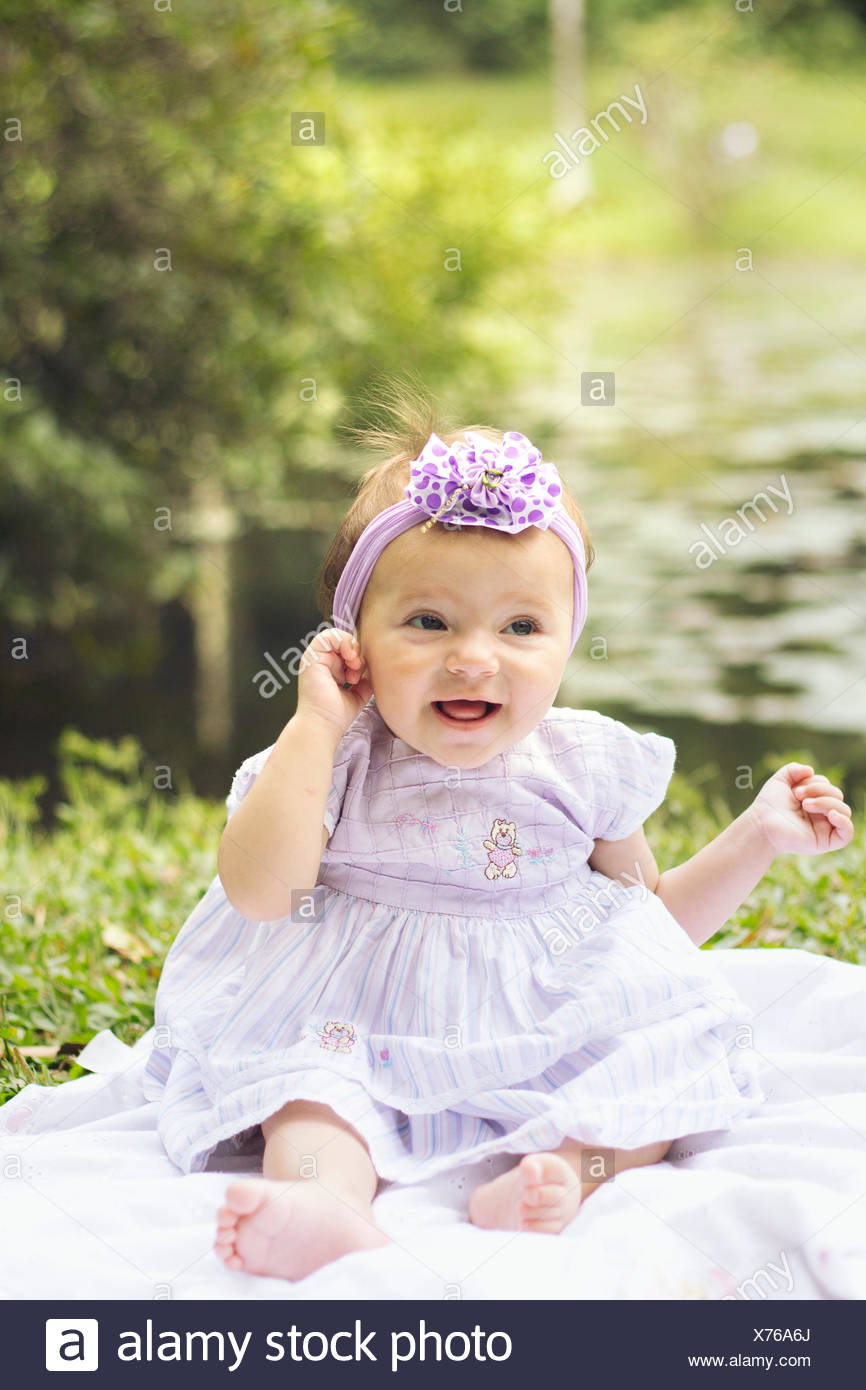 full length of a pretty baby girl sittingthe lake stock photo