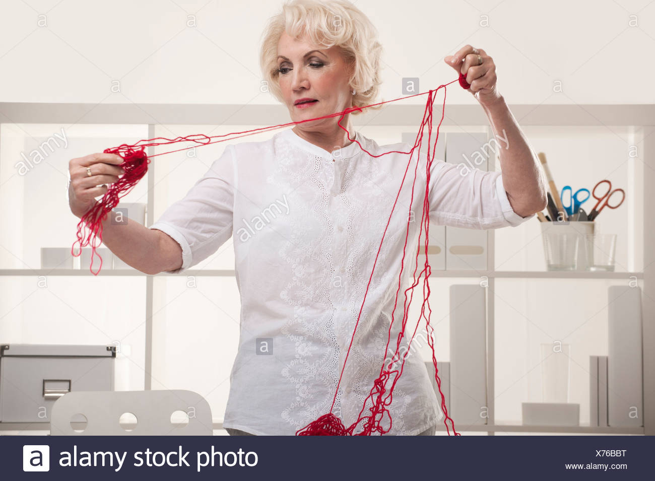 Senior woman with tangled wool - Stock Image