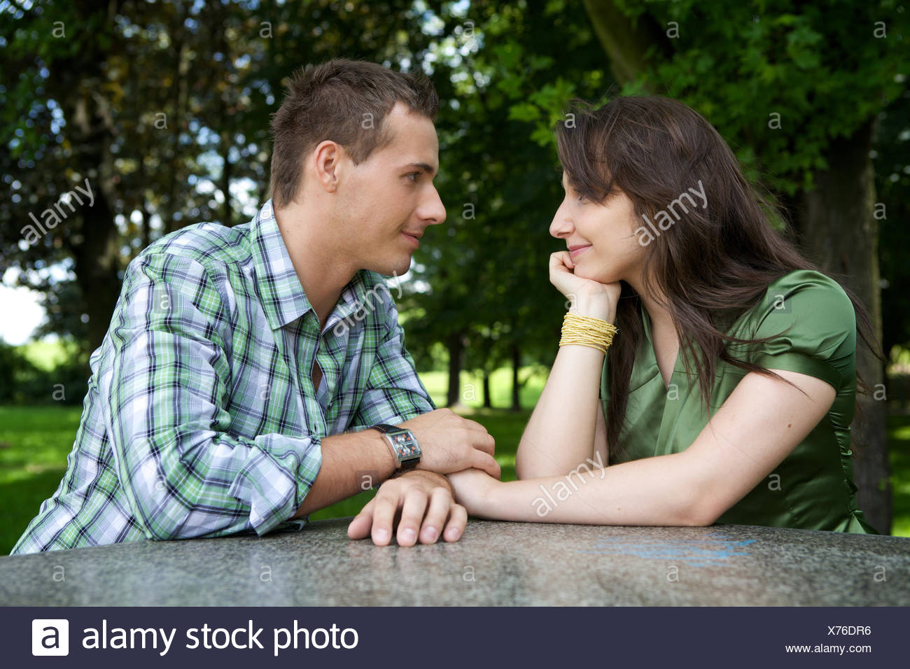 Young couple holding hands and looking at each other - Stock Image