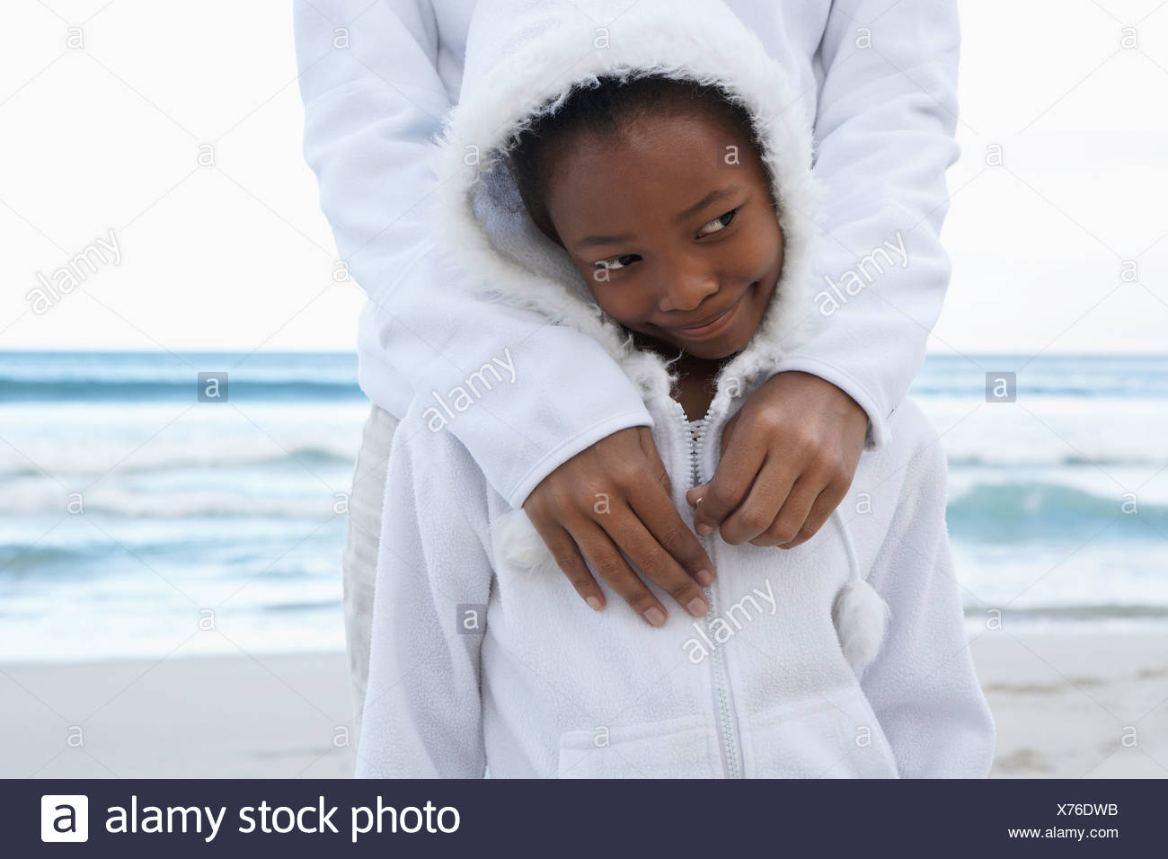 Mother and daughter 8 10 in white clothing standing on beach shy girl making sideways glance - Stock Image