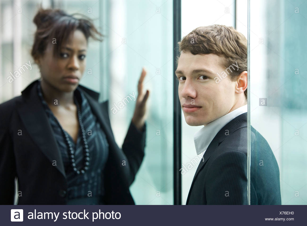 Businessman and businesswoman looking at camera with uncertainty - Stock Image
