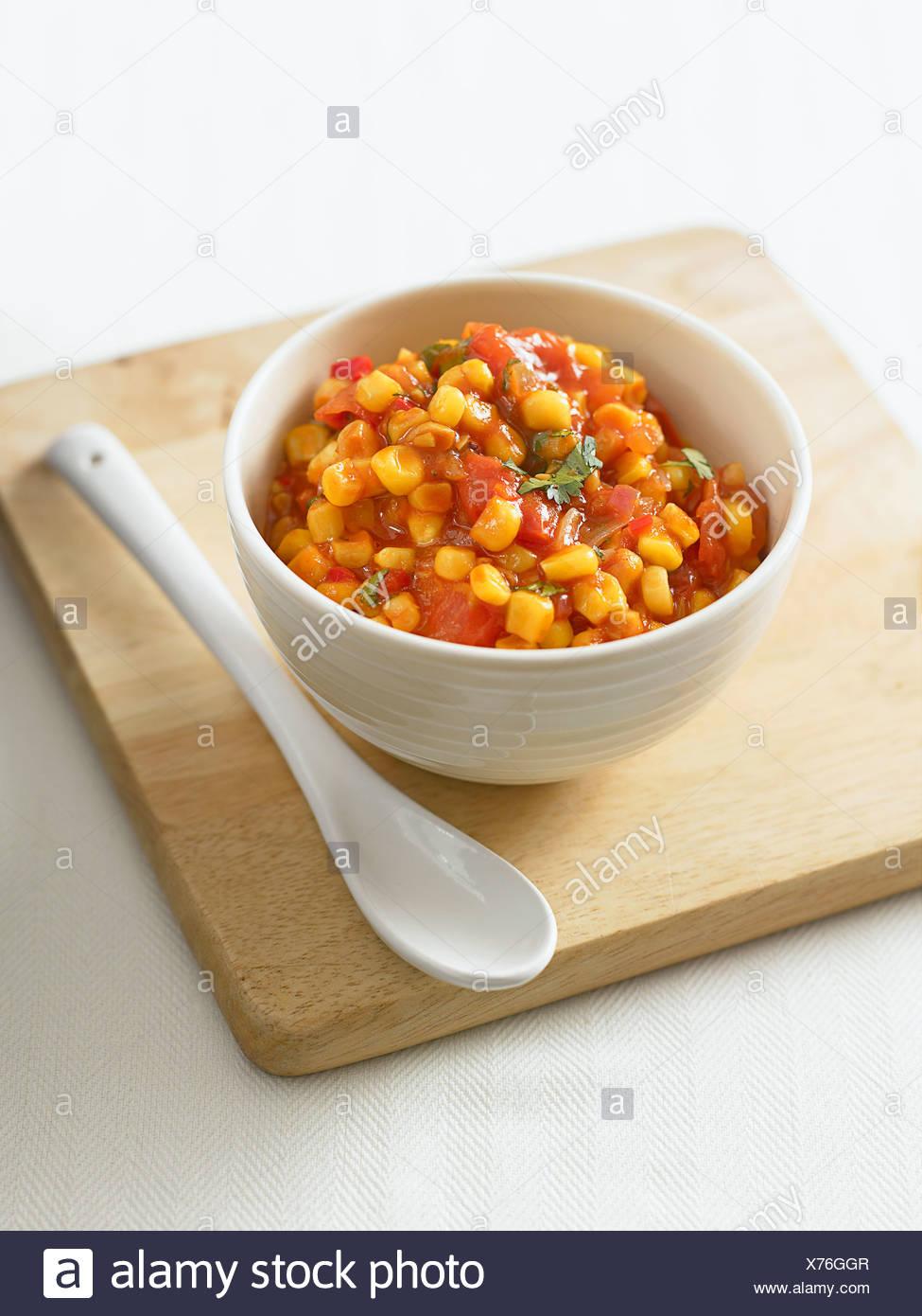 Bowl of corn relish on chopping board, close-up - Stock Image