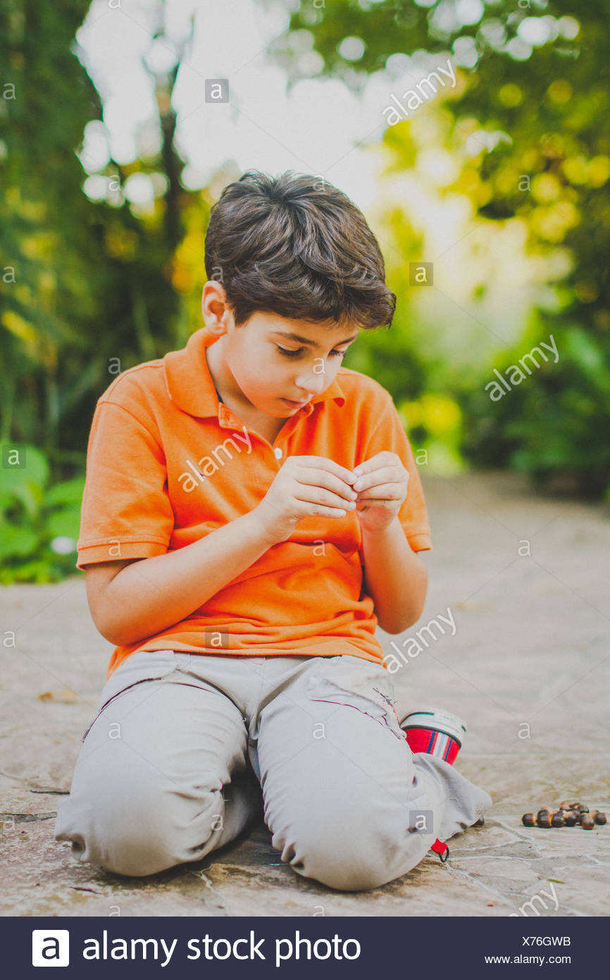 Portrait of boy (10-11) sitting on park alley, looking at plant seeds - Stock Image