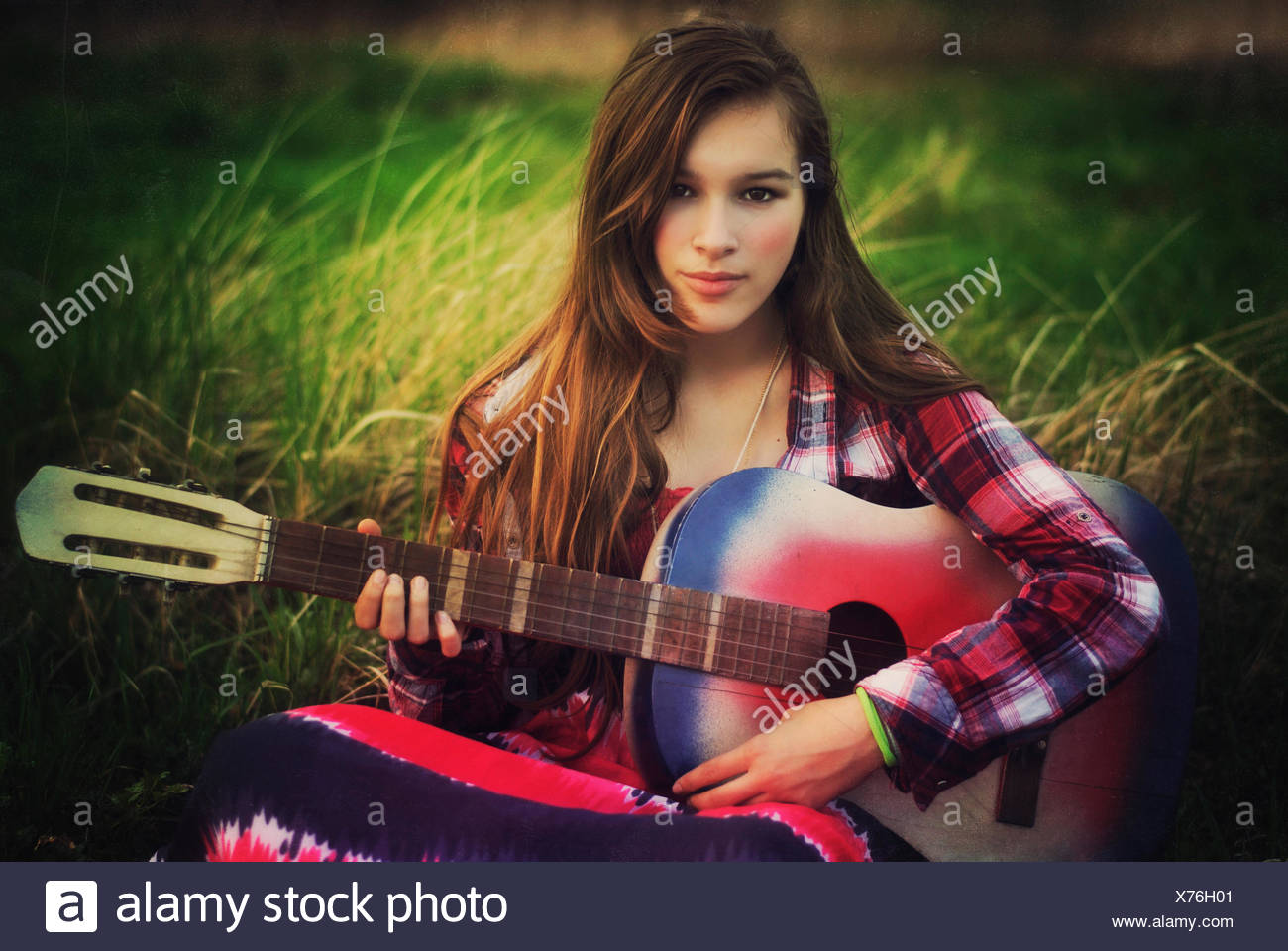 Portrait of a teenage girl sitting in a meadow with her guitar, Poland Stock Photo