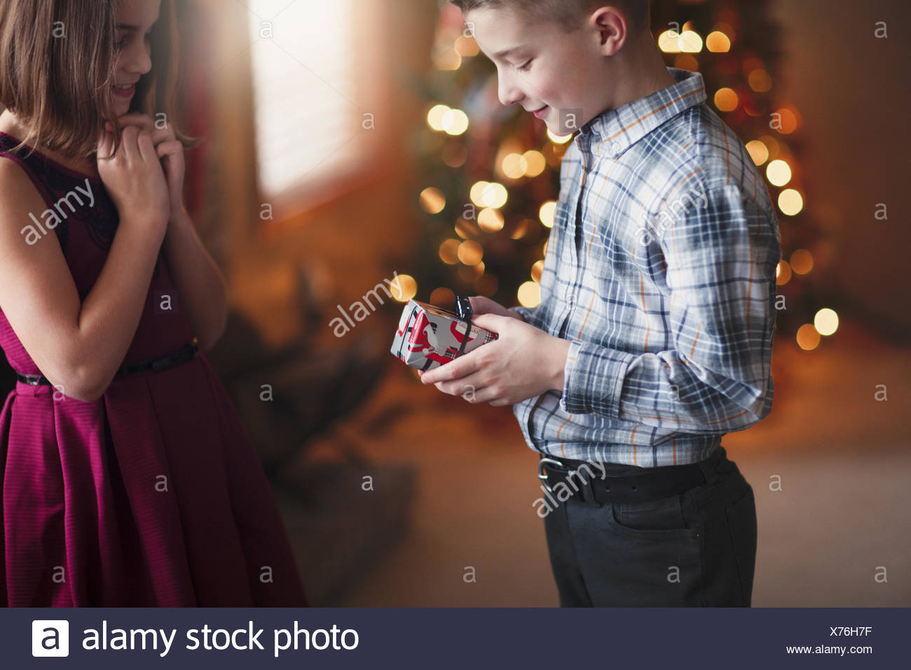 Brother and sister exchanging christmas gifts - Stock Image