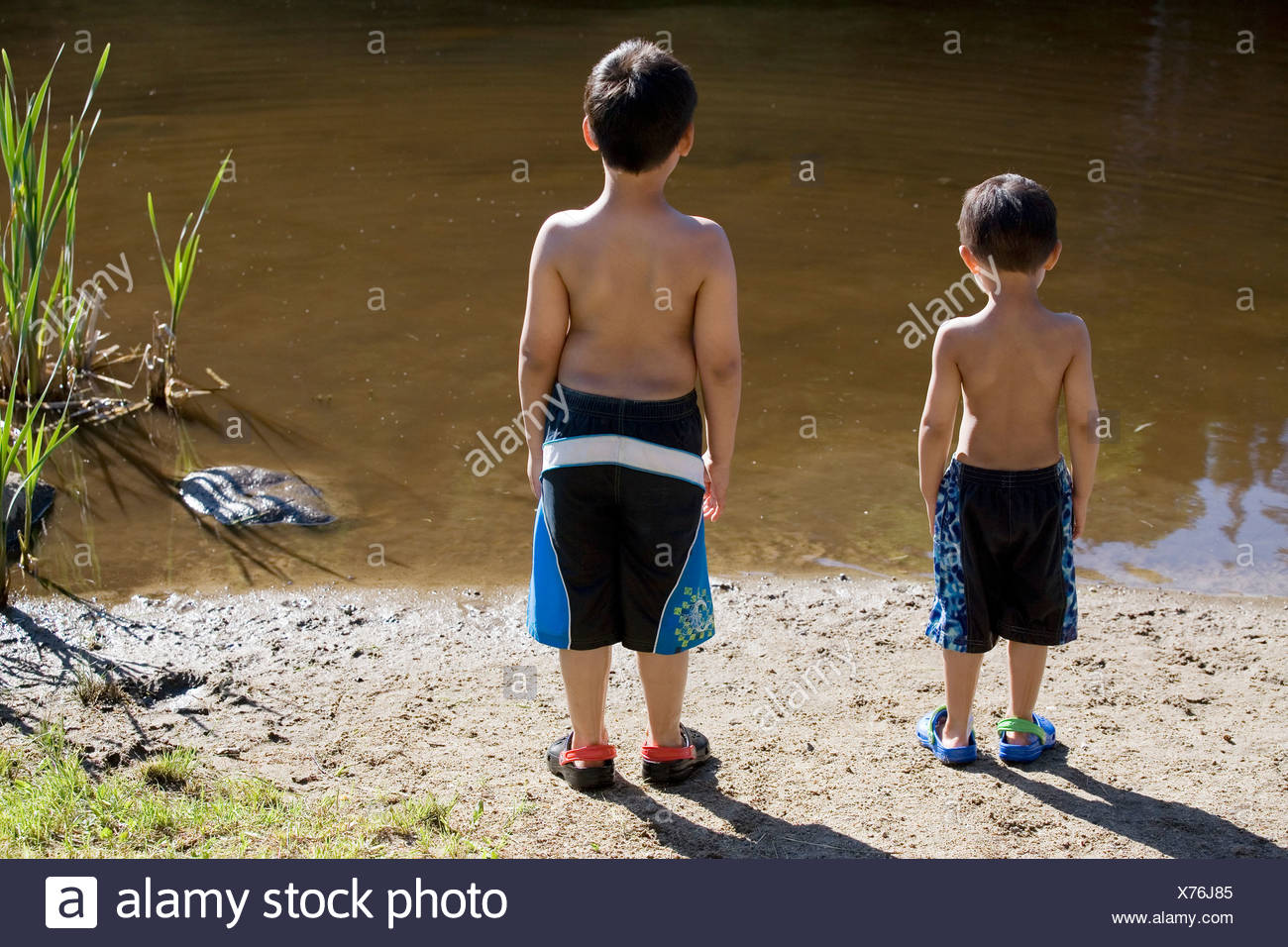 canadian born, vietnamese boys standing by the lakeshore, Val David, Quebec, Canada. - Stock Image