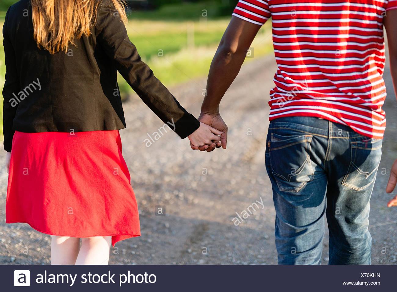 Sweden, Vastmanland, Bergslagen, Hallefors, Rear view of mid adult couple holding hands - Stock Image